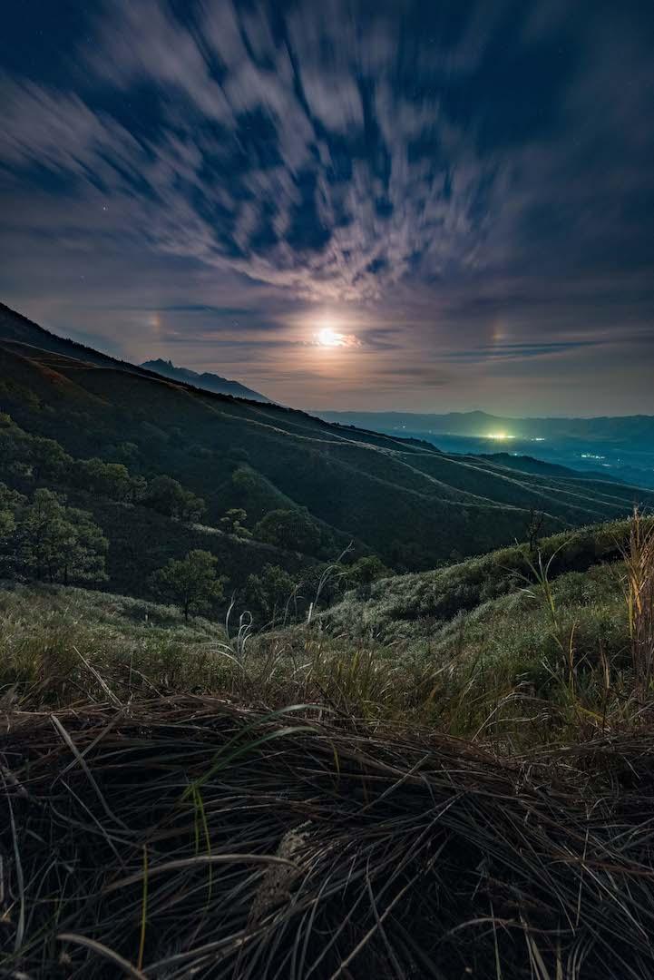 広大な草原とトレッキングコースに現れた幻月